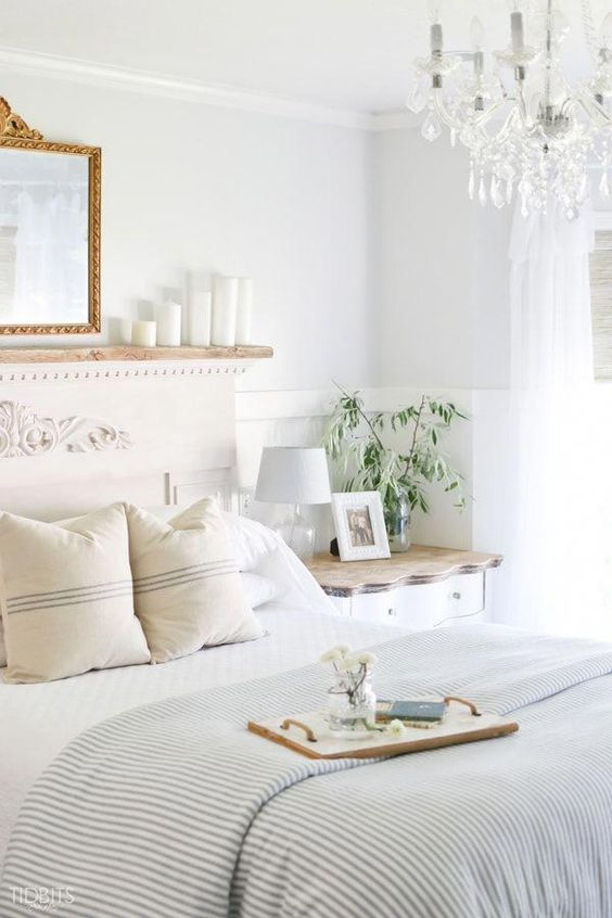 a relaxed summer bedroom with neutral wooden furniture, a mirror in a gilded frame, striped bedding and a crystal chandelier