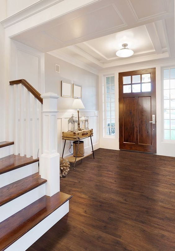a rustic entryway with a vinyl floor that imitates stained wood, a matching door, a suitcase console table and pretty lamps