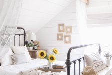 a rustic summer bedroom with a wooden beam with curtains, a metal bed with neutral bedding, a bench with decor and a small gallery wall