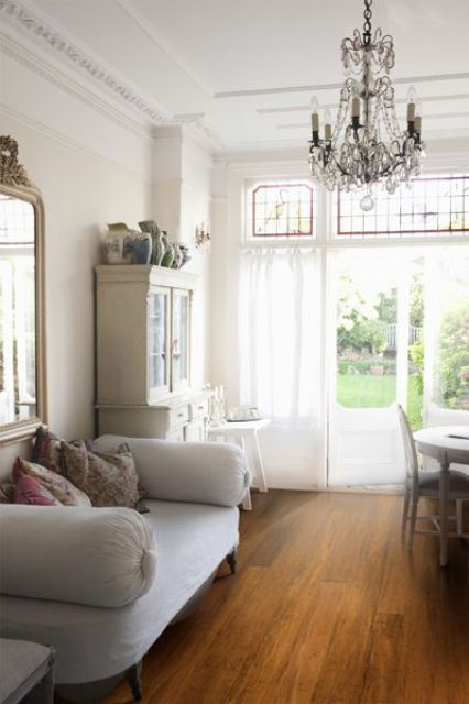 a shabby chic living and dining room with bamboo floors, white and neutral furniture, a crystal chandelier, a glazed wall with an entrance to the garden