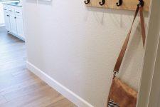 a simple and small entryway with white textural walls, a vinyl floor, a hanger, a mini gallery wall is a cozy space