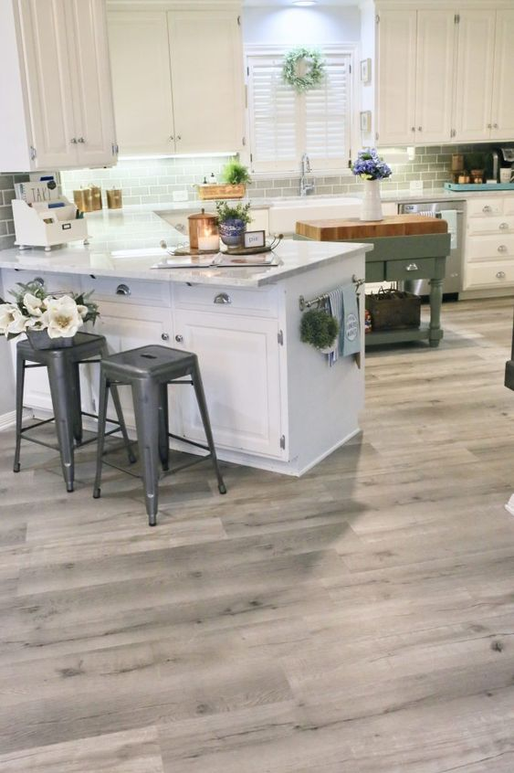 a simple farmhouse kitchen with a vinyl floor, white cabinets, a grey subway tile backsplash, metal stools and a green kitchen island