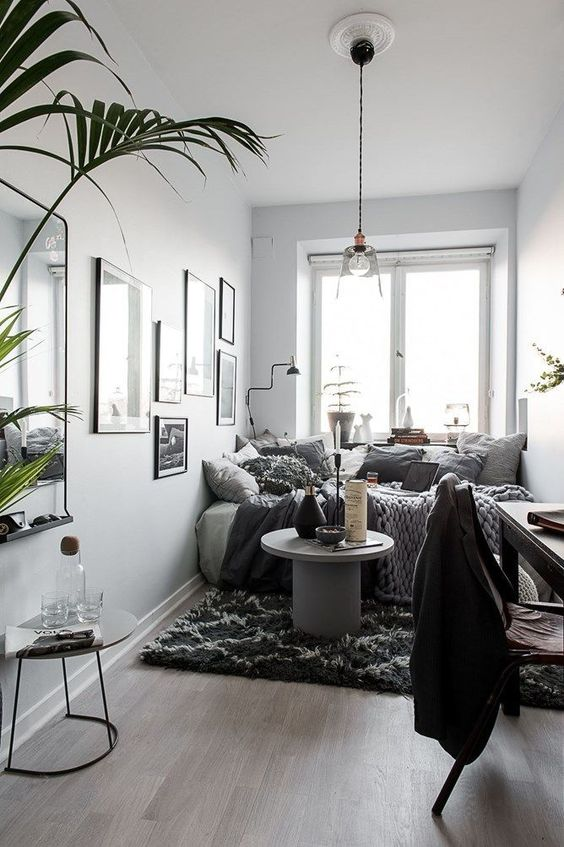 a small Nordic bedroom with white walls and a ceiling, a comfy bed with lots of pillows and potted plants, a black desk and a dark chair