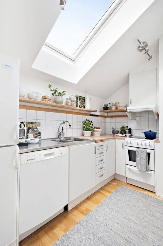 a small Scandinavian attic kitchen with butcherblock coutnertops, a skylight, open shelves and square tiles