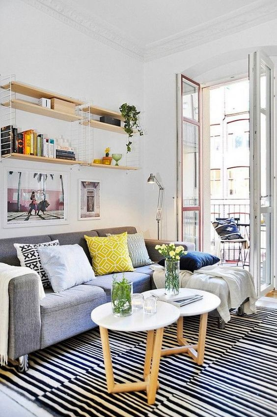 a small and bright summer living room with a grey sofa, round tables, open shelves and bright textiles
