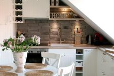 a small and lovely attic kitchen with planked cabinets, butcherblock countertops, a brick backsplash, a crystal chandelier and a white dining set