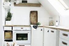 a small and neutral attic kitchen with white cabinetry and leather pulls, butcherblock countertops and a wooden slab shelf