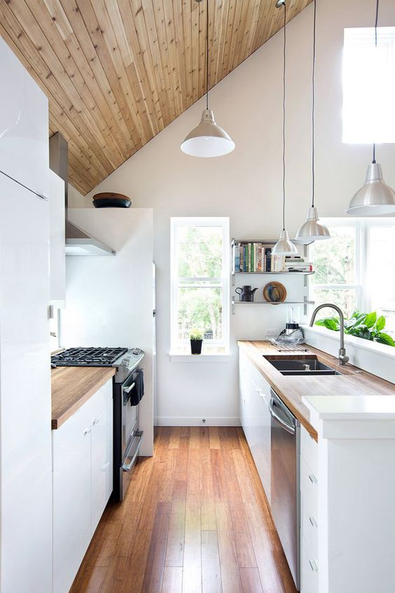 a small attic kitchen with a wood clad ceiling, white cabinets and butcherblock countertops, pendant lamps and lots of windows
