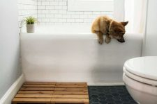 a small bathroom with white subway tiles and navy hexagon ones on the floor, a wooden bathmat and a potted plant is very cool