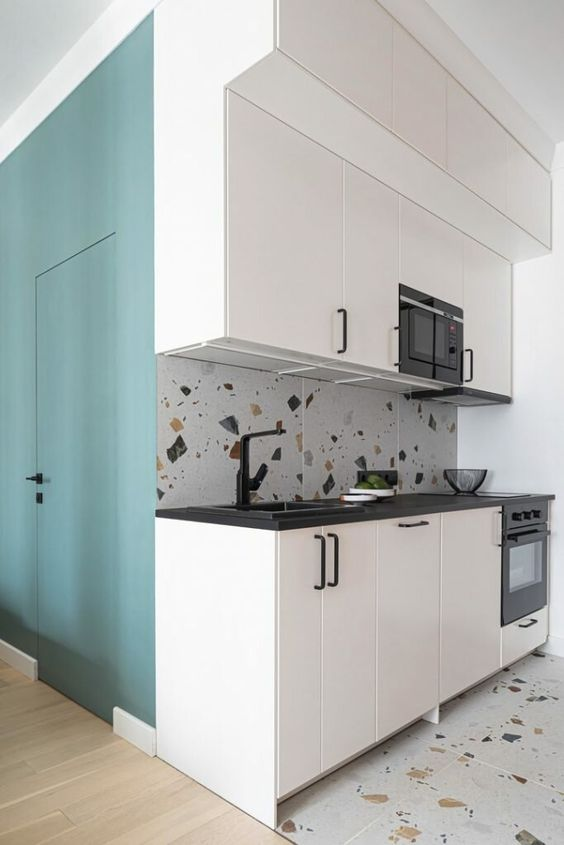 a small black and white kitchen with black handles and fixtures, a bright terrazzo backsplash and a matching floor for more fun