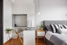 a small contemporary bedroom with a grey upholstered bed, chic bedding, a sleek storage unit in white with a built-in desk