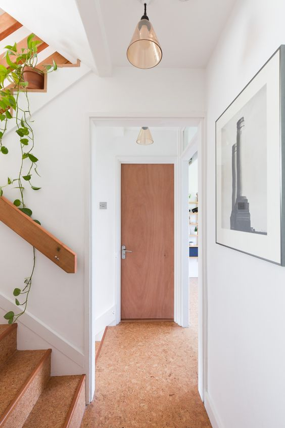 a small corridor with a cork floor and the same cover on the staircase is a chic idea that feels warm and natural