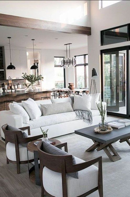 a small living room zone by a glass wall, with a white sofa and chairs, a concrete coffee table and neutral pillows