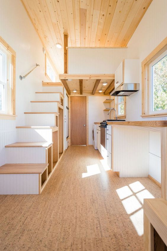 a small living space with a cork floor and a staircase with matching floor, with butcherblock countertops that echo in color