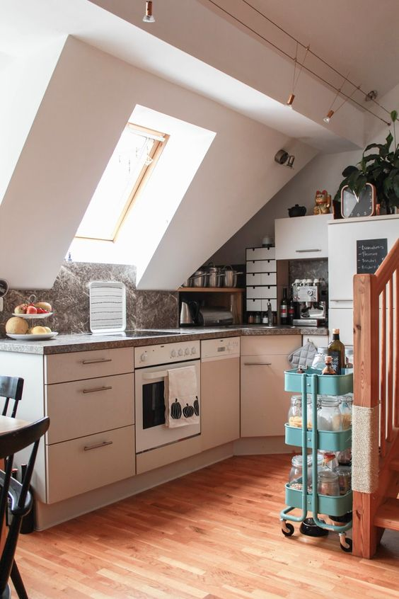 a small neutral attic kitchen with grey cabinets, grey stone countertops, a blue kitchen cart and pendant lights