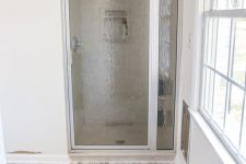 a small neutral bathroom with a shower space, a marble penny tile vinyl floor is a lovely and chic space to be