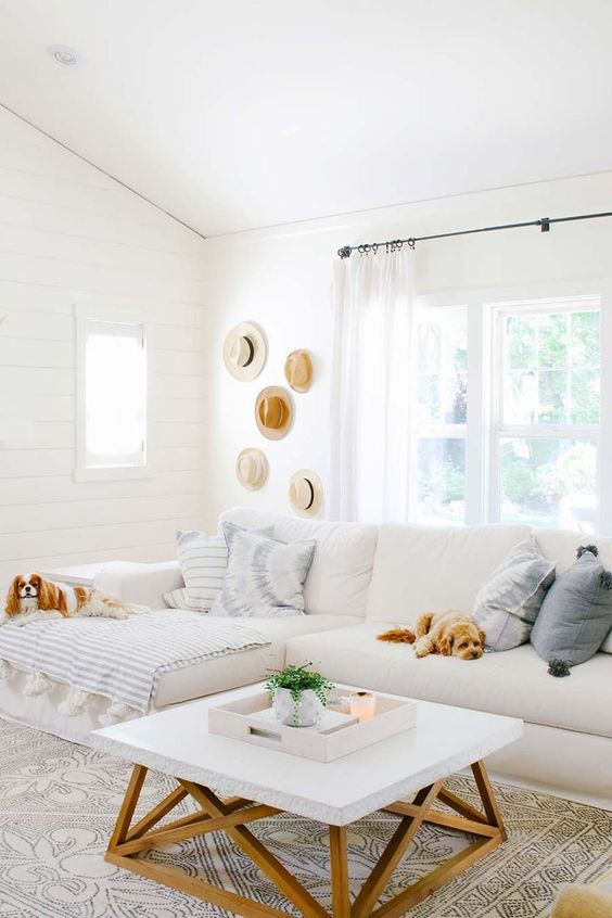 a small summer living room with white planked walls, a white sectional, a low coffee table, hats for decor and some striped textiles