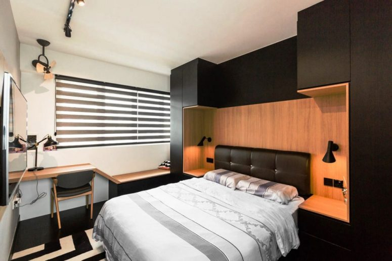 a small yet chic bedroom in black and light stained wood, with a leather bed built into a storage unit and a small floating desk