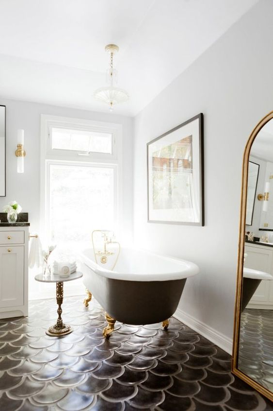 a sophisticated bathroom with white walls and a black fish scale tile floor, a refined black bathtub and lamps plus a floor mirror
