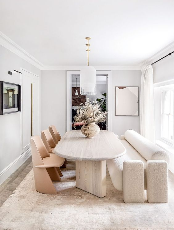 a sophisticated neutral dining room with an oval table, wooden chairs, a modern white sofa, pendant lamps is very chic
