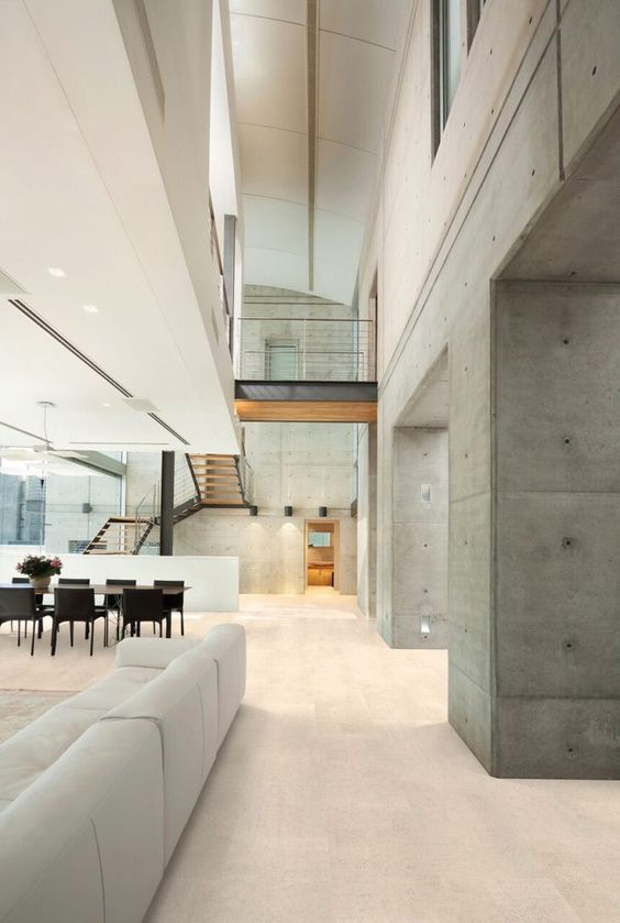 a sophisticated open layout with a living room and a dining space, with a cork floor and raw concrete walls is gorgeous