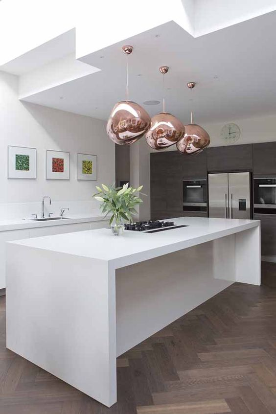a sophisticated white kitchen with dark parquet floors, sleke white cabinets, grey ones with built-in appliances and copper lamps