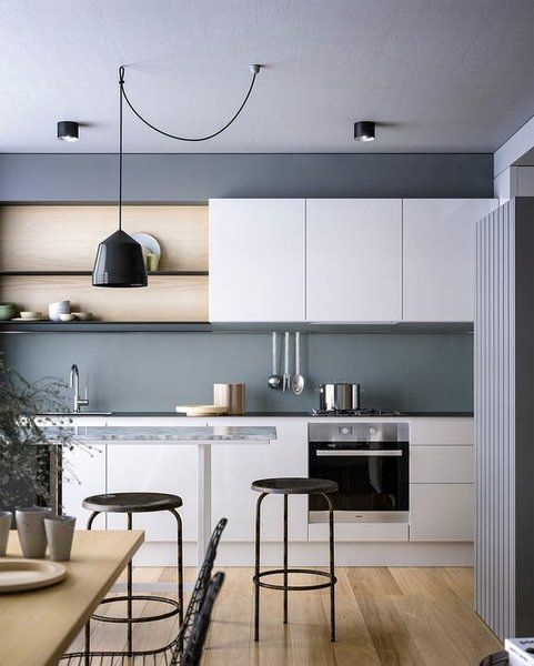 a stylish Scandinavian kitchen with sleke white cabinetry, a wooden table and round stools, a pendant lamp and cool lights