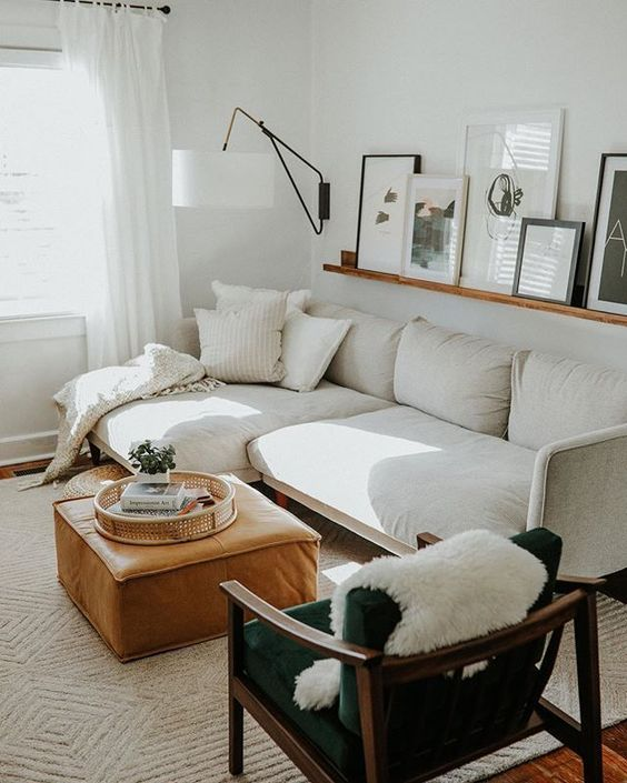 a stylish Scandinavian living room with a white sofa, a green chair, an amber leather ottoman, a ledge with artworks and a cool sconce