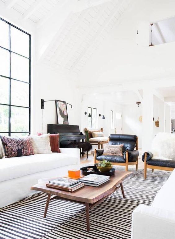 a stylish Scandinavian living room with two white sofas, a live edge table, a striped rug and black leather chairs