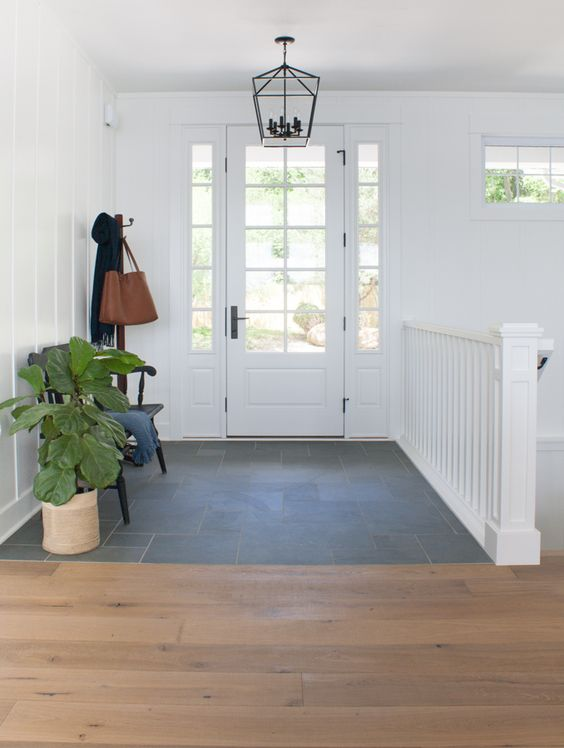 a stylish and airy entryway with a tile and laminate floor, a small black bench and a potted plant plus a pendant lamp