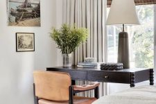 a stylish bedroom done in neutrals, with a black desk and a leather chair for working placed by the window