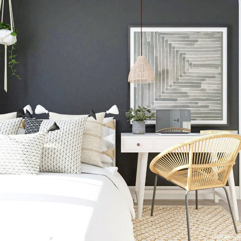 a stylish bedroom with black walls, white furniture, a rattan chair, an abstract artwork is an office bedroom combo