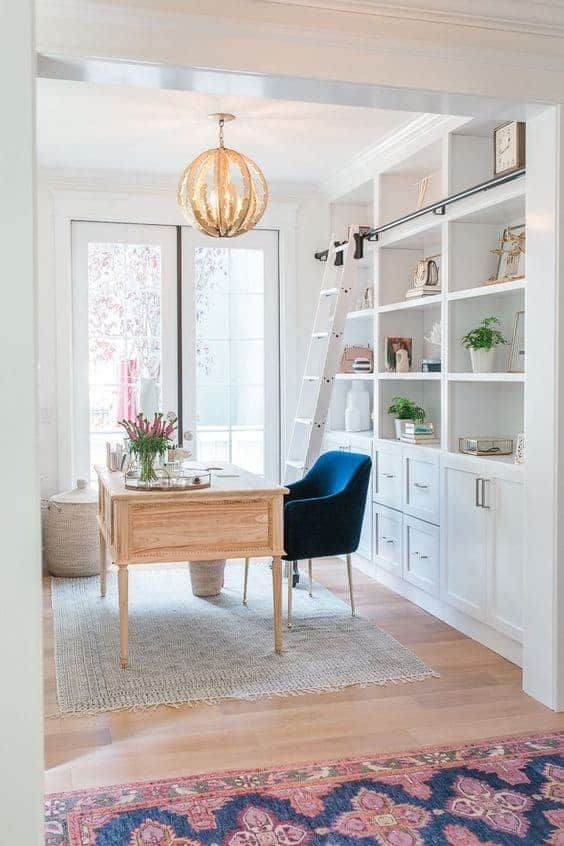 a stylish coastal farmhouse home office with a white built-in storage unit, a ladder, a wooden desk and a navy chair, a catchy lamp