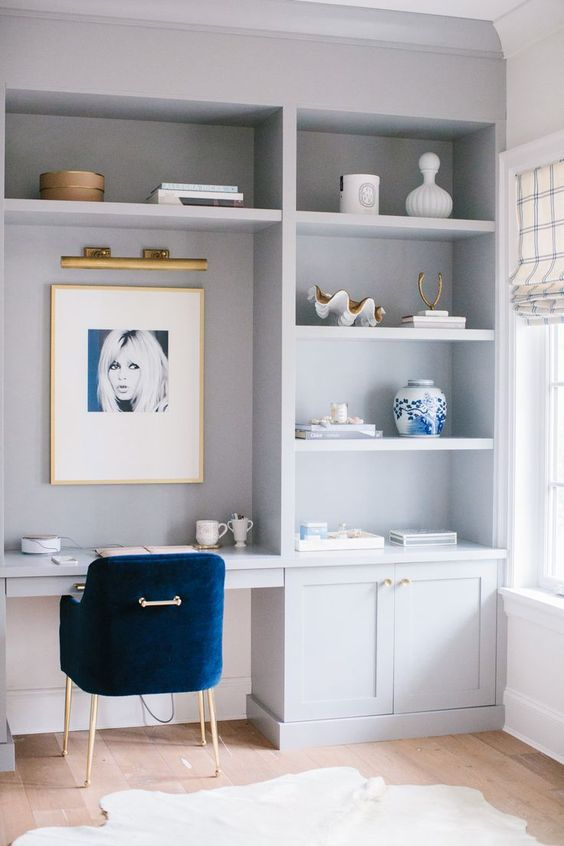 a stylish coastal home office in dove grey, with a large storage unit and a built-in desk, shelves, an artwork and a pretty navy velvet chair