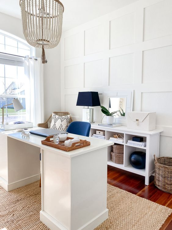 a stylish coastal home office with white paneling on the wall, white furniture, a navy chair, a lamp and a wooden bead chandelier