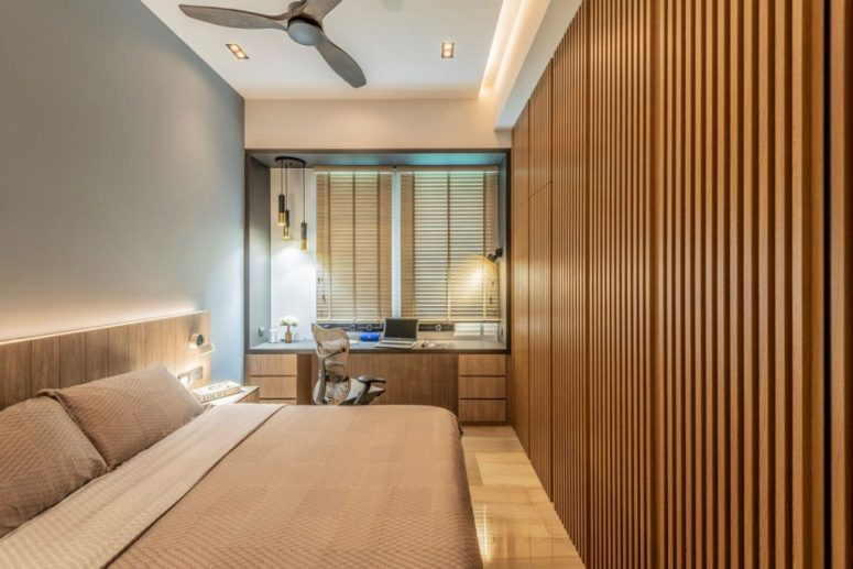 a stylish contemporary home office with a blue accent wall, a large bed and a built-in storage unit clad with wooden slabs, a windowsill desk