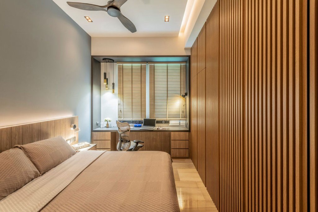a stylish contemporary home office with a blue accent wall, a large bed and a built in storage unit clad with wooden slabs, a windowsill desk