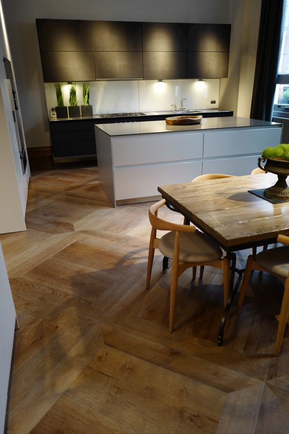 a stylish contemporary kitchen with sleek black cabientry, a white kitchen island, a wooden table and chic chairs plus a parquet floor