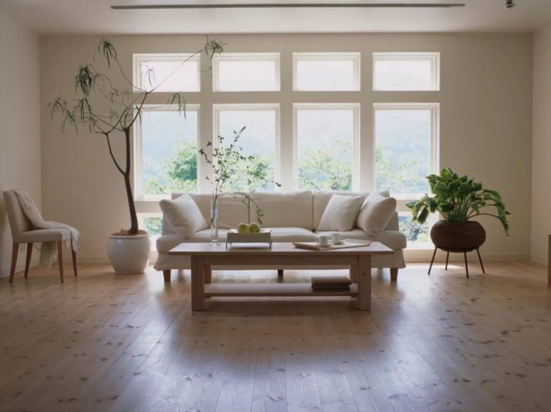 a stylish contemporary living room with several windows, a white sofa and chair, a wooden coffee table and statement plants plus laminate floors