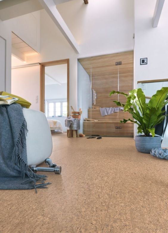 a stylish contemporary space with white walls, a cork floor, chic furniture, potted plants and a private sauna clad with glass
