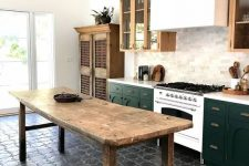 a stylish eclectic kitchen with stained and dark green cabinets, dark grey floor tiles, a vintage wooden kitchen island