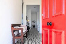a stylish entryway with a black and white vinyl floor, a red door, a vintage dark stained bench and a chic chandelier