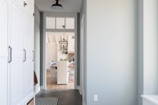 a stylish farmhouse entryway with grey walls and a grey tile floor, white farmhouse storage cabinets and baskets for storage