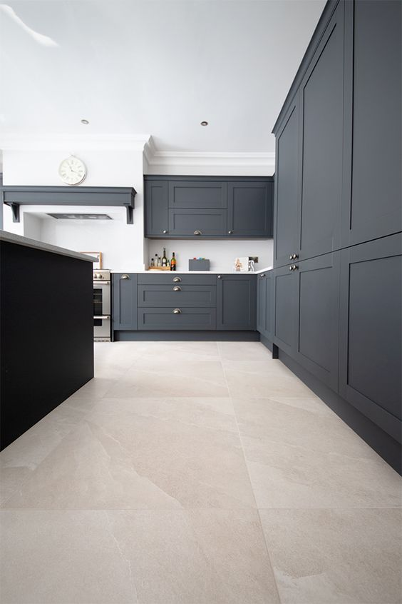 a stylish farmhouse kitchen with graphite grey cabinetry, a tile floor, a black kitchen island and white countertops is chic