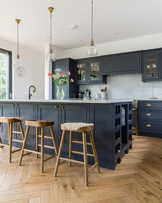 a stylish farmhouse kitchen with light stained parquet flooring, navy cabinets, wooden stools, pendant lamps and brass touches