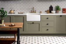 a stylish farmhouse olive green kitchen with white subway tiles and a pretty tile floor plus a rustic dinign set is wow