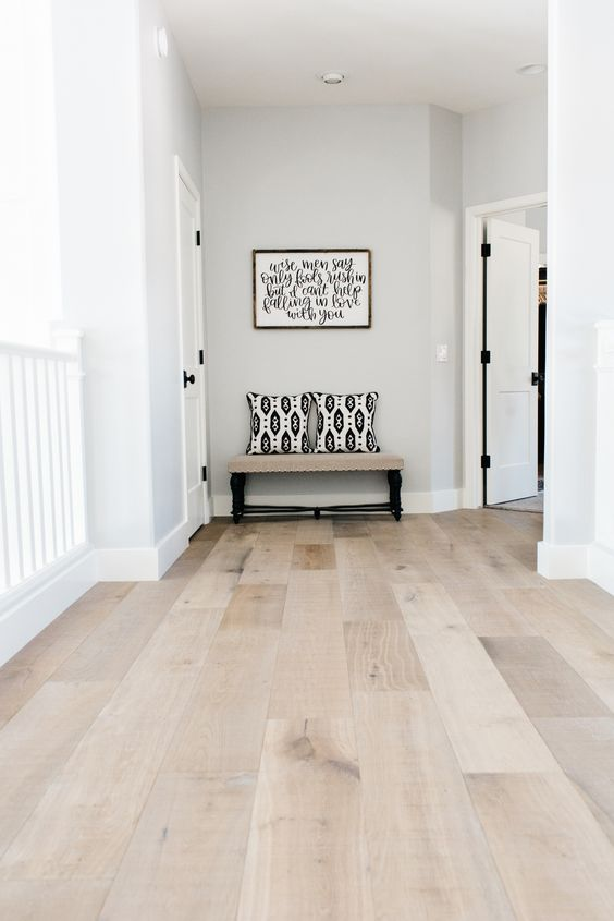a stylish modern entryway with grey walls and neutral laminate floors, a bench with pillows is cool and welcoming