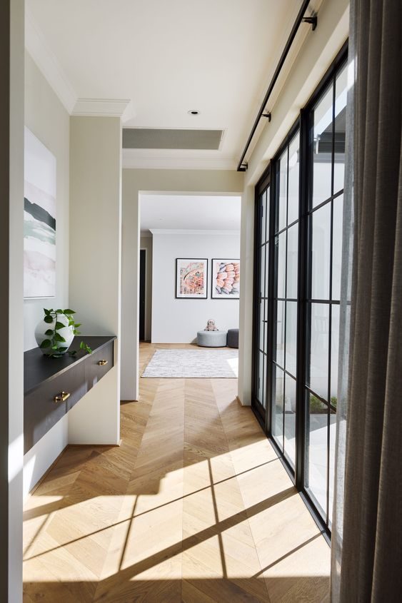 a stylish space with a neutral parquet floor, a black built-in console table and a lovely watercolor artwork