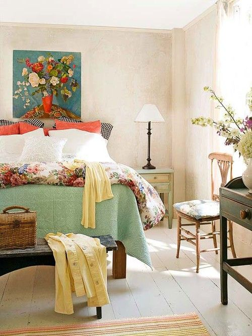 a stylish vintage summer bedroom with tan walls, wooden vintage furniture, bright textiles and floral upholstery, a floral artwork and yellow touches