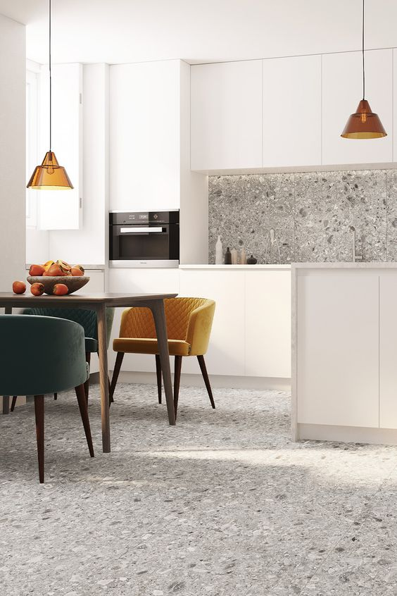 a stylish white kitchen with sleek cabinetry, a grey terrazzo backsplash and a matching floor for a more cohesive look